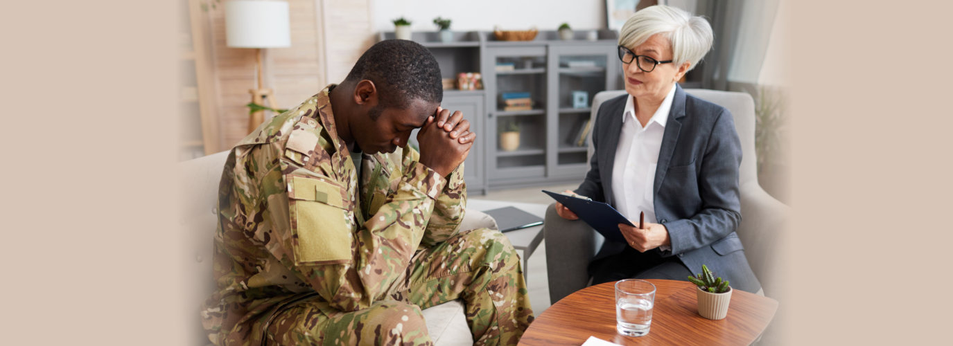 Depressed young military man sitting on sofa during therapy session with psychologist
