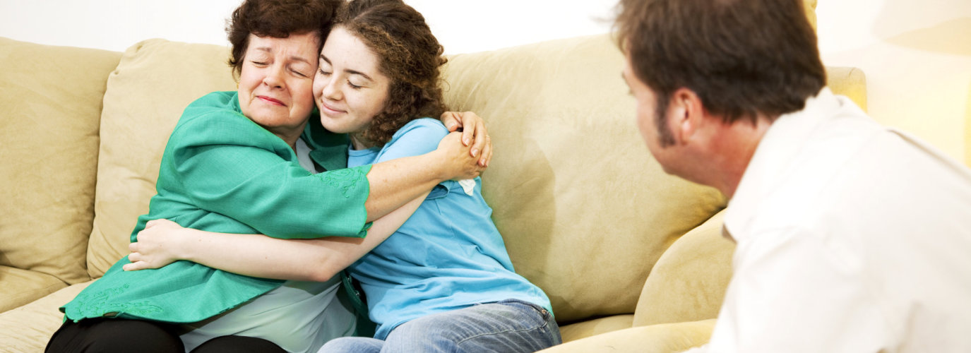 Mother And Daughter Hugging During A Family Counseling